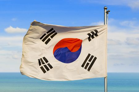 south korean flag on a pole against beautiful sky over horizon on water photo