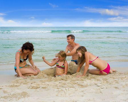 koh: familia feliz en vacaciones jugando en la playa, lanzando arena unos a los otros