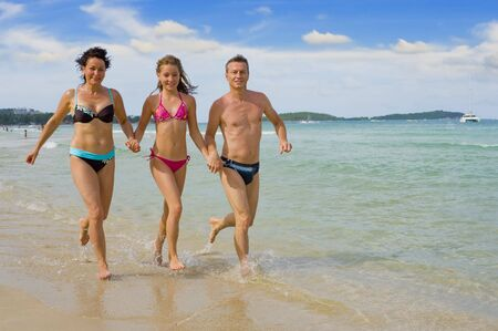 parents with daughter running at chaweng beach in samui island, thailand photo