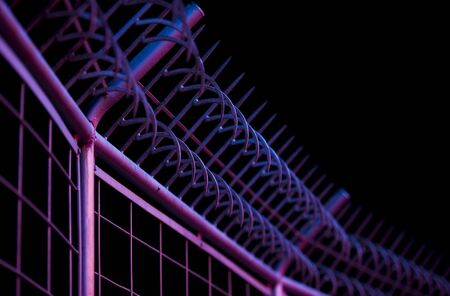 iron barred: safety bars with hooks with reflected neon lights. photographed with a shallow depth of field. Stock Photo