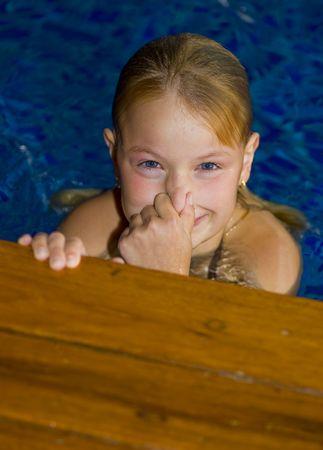 cute preteen having fun in a swimming pool photo