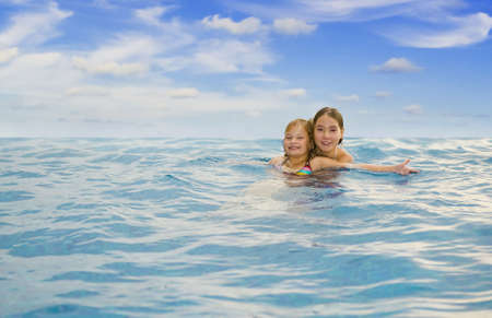 two sister girls swimming in the sea photo