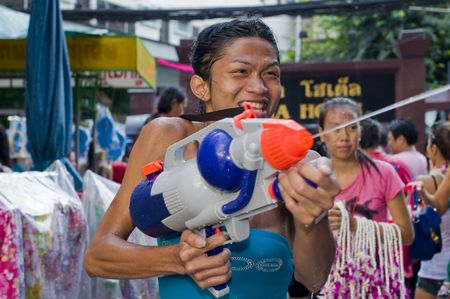 watergun: BANGKOK - APRIL 15: Thai shemale celebrating Songkran (Thai new year  water festival) in the streets by shooting water at other people on April 15, 2010 in Bangkok, Thailand.  Editorial