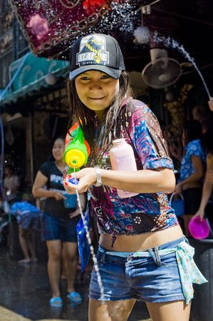 water gun: BANGKOK - APRIL 13: Thai woman celebrating Songkran (Thai new year  water festival) in the streets by shooting water at other people on April 13, 2010 in Bangkok, Thailand.  Editorial