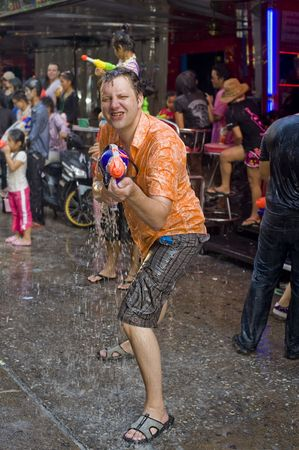 BANGKOK - APRIL 13: Foreigner celebrating Songkran (Thai new year / water festival) on the street by shooting with his water gun - on April 13, 2010 in Bangkok, Thailand.