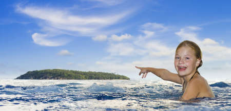 girl in the sea pointing to an island at the horizon photo