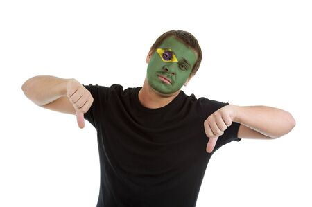 man with brazilian flag painted on his face showing two thumbs down, isolated on white background photo