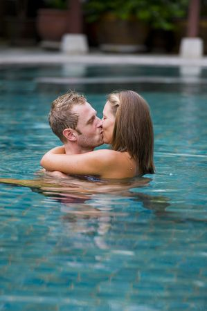 man and woman kissing each other in a swimming pool