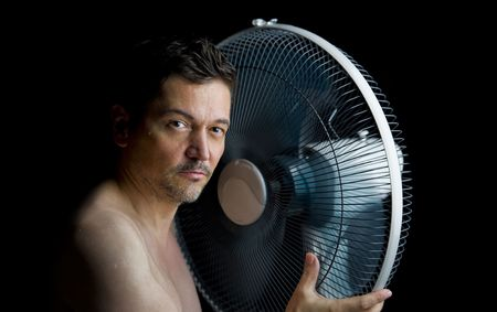 heat wave - sweaty man with fan isolated on black background photo