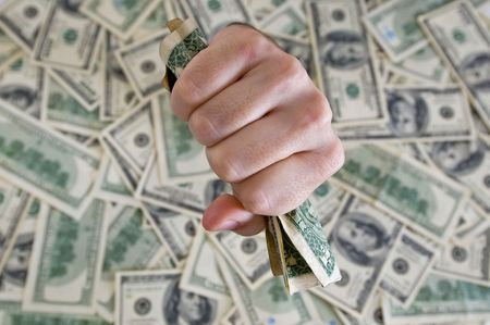 a fist with dollars breaking through a dollar background photo