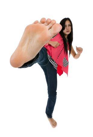 self defense: pretty woman kicks with her foot, isolated on white background with a shallow depth of field focussed on the foot Stock Photo