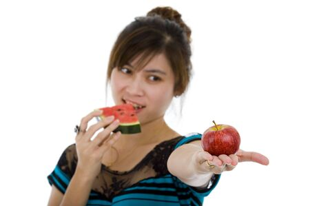 beautiful asian woman with an apple and a slice of a water melon, isolated on white background with a shallow depth of field, focused on the apple. Stock Photo - 7488573
