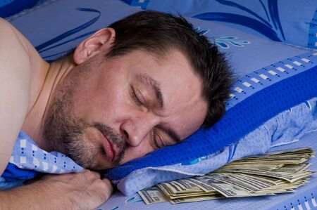 man sleeping with money under his pillow  Stock Photo
