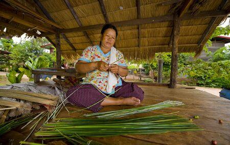 beach mat: an asian woman making straw mats by hand