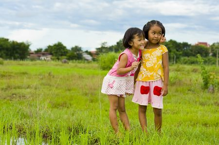 cute girl holding a grasshopper in her hand showing her friend something photo