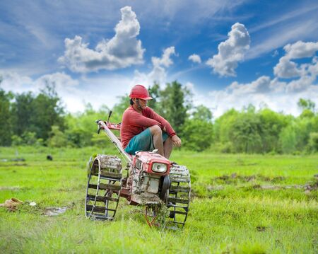 plow man in the rice fields taking a break sitting on his vehicle Stock Photo - 7601818