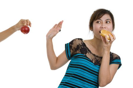 young asian beauty refusing an apple prefering a hamburger, isolated on white background photo