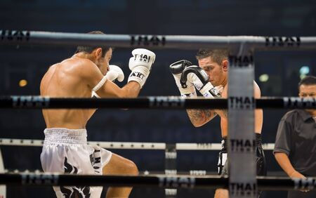 thai language: BANGKOK, THAILAND - AUGUST 29, 2010: English thaiboxing world champion Liam Harrison in an international fight competition against Rafighdoust Behzan from Iran. Editorial