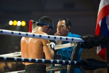 show ring: BANGKOK, THAILAND - AUGUST 29, 2010: Thaiboxing champion Petchmonkong Petchfocus praying with his coach before a fight in an international competition.