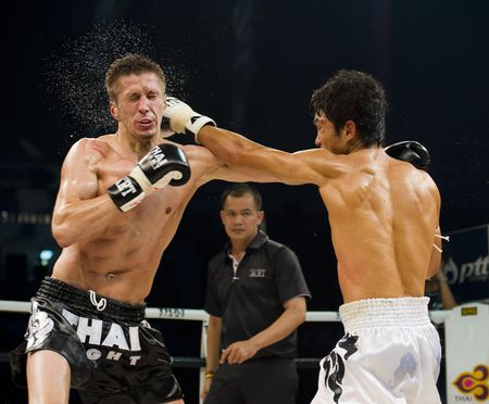 BANGKOK, THAILAND - AUGUST 29, 2010: Hurkou Vital, thai boxer from russia, got hit by his opponent Hyun Ko Jong from korea. shot in an international fight competition.