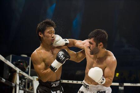 arbitri: BANGKOK, Thailandia - 29 agosto 2010: Arican Fikri, pugile tailandese dalla Turchia colpisce il suo avversario Miyakoshi Soichiro. girato in un concorso internazionale di lotta.  Editoriali