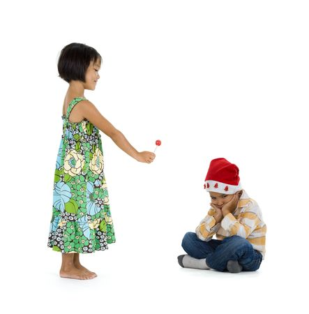 a little girl giving her friend a lollipop for christmas. they boy doesnt appreciate it at all. isolate on white background. photo