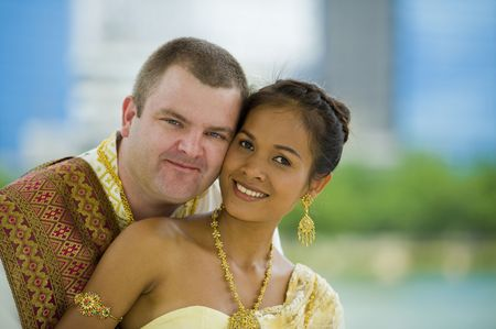 interracial marriage: Fortunatamente la coppia sposata in abiti tradizionali tailandese nozze posano in un parco Archivio Fotografico
