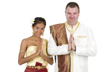 interracial marriage: Fortunatamente la coppia sposata in abiti tradizionali tailandese nozze, isolati su sfondo bianco