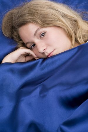 teeny: teenage girl laying in bed covered with blue silk sheet Stock Photo