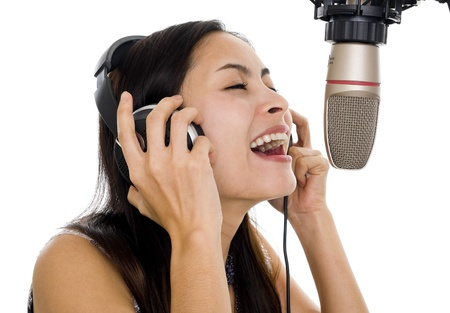 micro recording: beautiful woman recording vocals in music studio, isolated on white background
