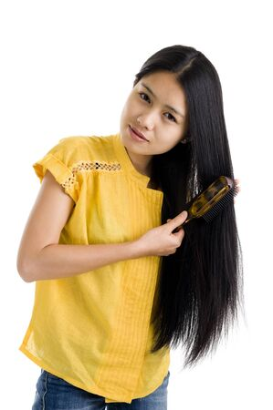 hairbrush: pretty woman brushing her long hair, isolated on white background