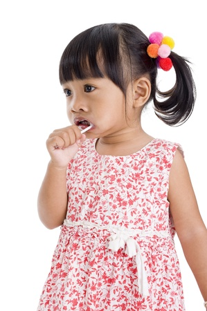 cute little girl with a lollipop isolated on white background photo
