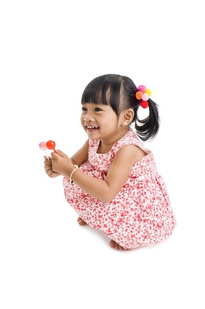 cute little girl with two lollipops isolated on white background photo