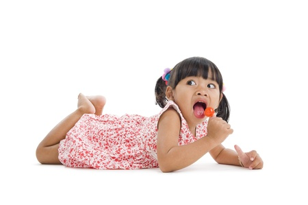 licking in isolated: carino bambina con un lecca-lecca isolato su sfondo bianco Archivio Fotografico