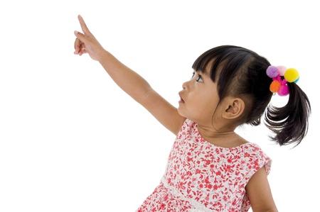 ragazza che indica: dolce bambina che punta a qualcosa, isolato su sfondo bianco
