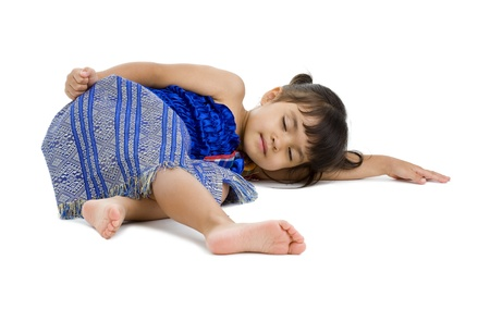 cute little girl laying on the floor with eyes closed, isolated on white background