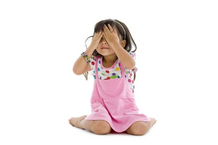 cute little girl covering her eyes with her hands, isolated on white background