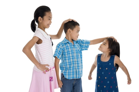 taller: children with different sizes, isolated on white background Stock Photo