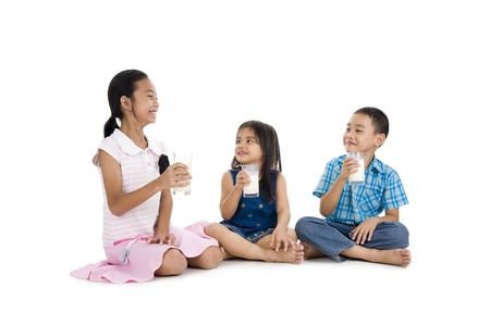 siblings drinking milk, isolated on white background photo