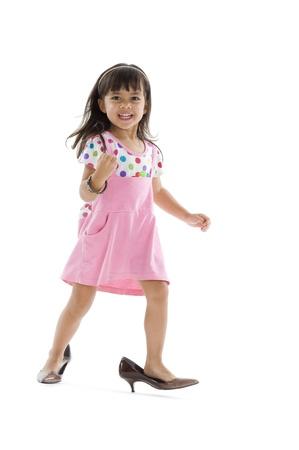 przewymiarowany: Cute maÅ'e dziecko ze zbyt duży buty, samodzielnie na biaÅ'ym tle Zdjęcie Seryjne