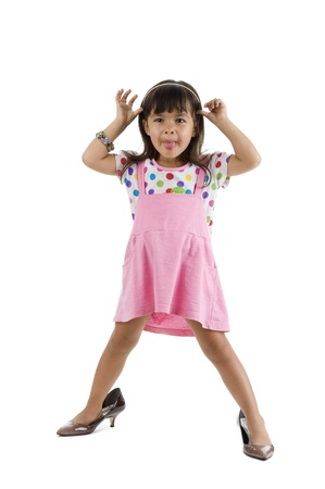 cute little girl with oversized shoes sticking out her tongue, isolated on white background