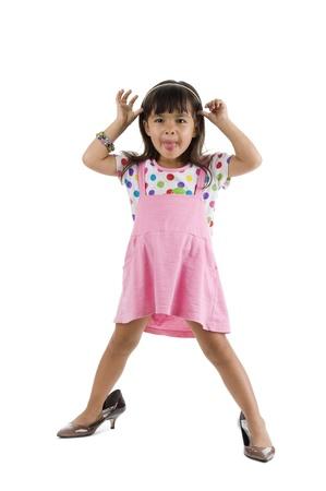 przewymiarowany: Cute little girl z zbyt duży buty pokazanie swojego języka, samodzielnie na białym tle