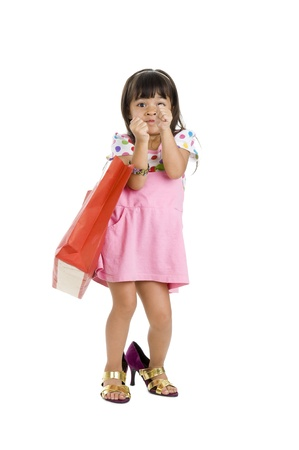 cute little girl with shopping bag and oversized shoes, isolated on white background photo