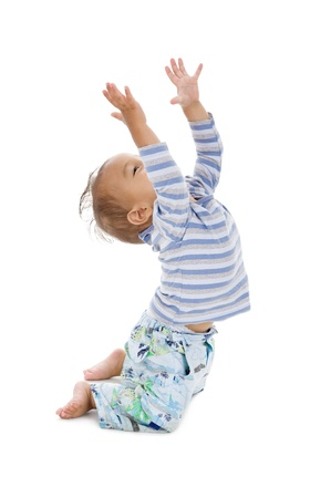 cute little boy trying to catch something coming from the top, isolated on white background photo