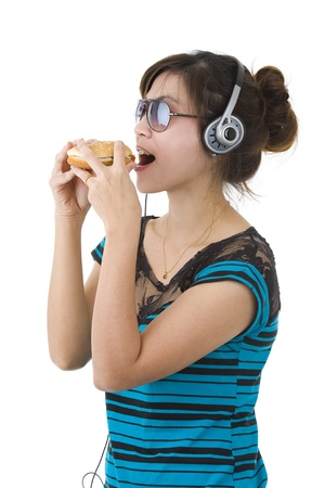 pretty woman with hamburger, sunglasses and head phones over white photo