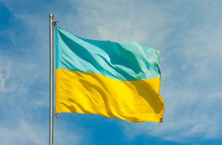 ukranian flag on a pole over beautiful sky