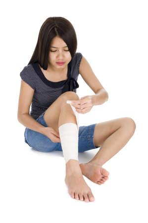 primeramente: mujer envoltura un vendaje alrededor de su pierna, aislado en fondo blanco