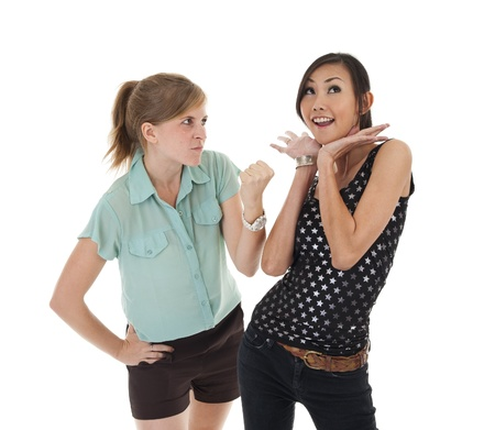 woman threatening her friend who is playing the innocent, isolated on white background photo