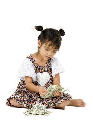 contando dinero: ni�a sentada en el suelo contando dinero, aislada sobre fondo blanco Foto de archivo