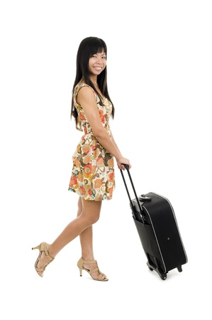 young asian woman posing with her hand luggage, isolated on white background photo